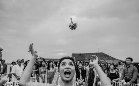 A bride throws her bouquet during a ceremony at Sri Panwa Resort, Phuket, Thailand. Photo: Wainwright Weddings